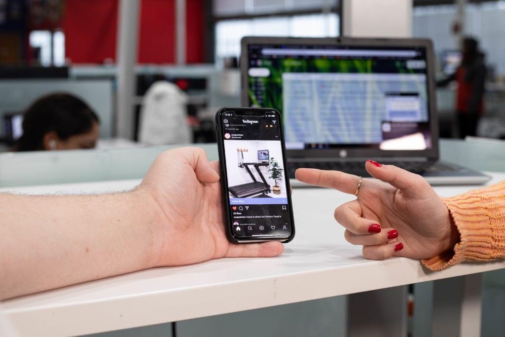 social media marketers look at phone
