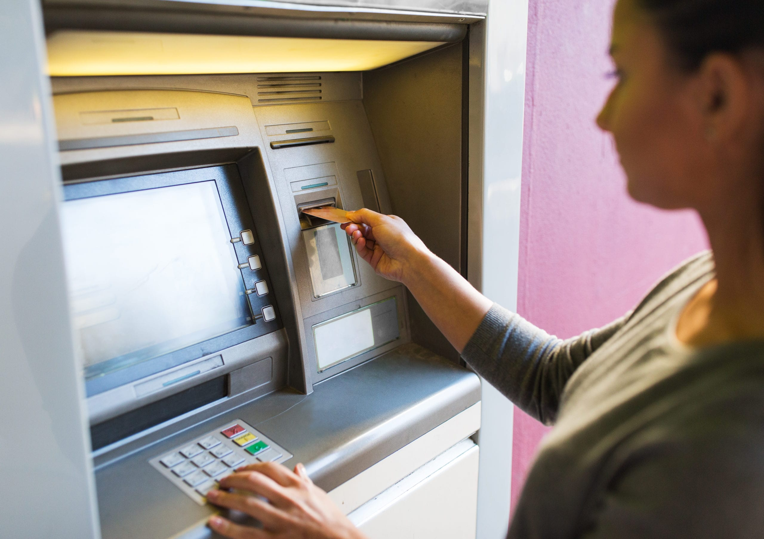 woman uses atm machine at bank